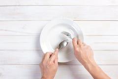 Mänsklig hand som rymmer en gaffel och en sked Fotografering för Bildbyråer