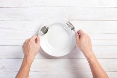 Mänsklig hand som rymmer en gaffel och en sked Arkivbild