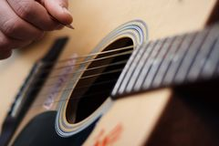 Mänsklig hand som rymmer en medlare för att spela på en akustisk gitarr royaltyfri bild