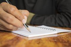 Mänsklig hand som skriver en anmärkning Arkivfoton