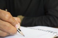 Mänsklig hand som skriver en anmärkning Arkivbild