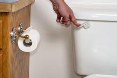 Mänsklig hand som spolar en toalett Arkivfoto
