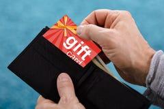Mänsklig hand som tar bort gåvakortet från plånboken royaltyfria foton