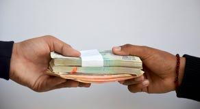 Mänsklig hand som till varandra ger indisk valuta Arkivfoto