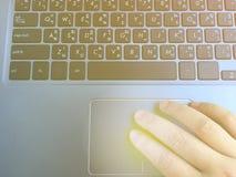 Mänsklig hand som trycker på på bärbar datortrackpad för markörrörelse arkivbilder