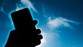 Mänsklig handinnehavsmartphone över bakgrund för blå himmel, telefonutstrålningsbegrepp royaltyfri fotografi
