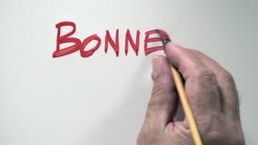 Mänsklig NOEL för handhandstilord JOYEUX i franskt, med röd gouache stock video