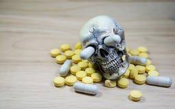 Mänsklig skalle i högen av droger, sjukdomen och fara Arkivbilder