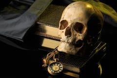 Mänsklig skalle på en bok bredvid klockan Begrepp Royaltyfri Fotografi