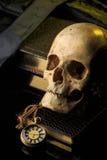 Mänsklig skalle på en bok bredvid klockan Begrepp Royaltyfria Bilder