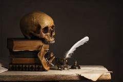 Mänsklig skalle på gamla böcker med den tomma sidan, fjädern och inkpoten royaltyfri bild