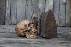 Mänsklig skalle på golvet med den gamla gamla wood ugnen, stilleben Royaltyfria Bilder