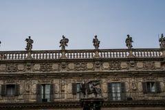 Mänsklig staty överst av arkitektonisk gammal byggnad Arkivfoton