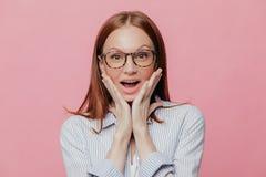 Mänskliga ansiktsuttryck, reaktionsbegrepp Den härliga blomstrande affärsdamen håller båda händer på kinder, bär elegant vit arkivbild