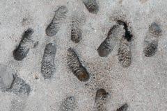 Mänskliga fotspår i betongen på stranden Arkivbilder