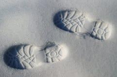 Mänskliga fotspårkängor reflekterade på den vita snön övervintrar arkivfoto