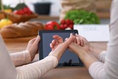 Mänskliga händer av två kvinnliga personer som använder touchpaden i köket Closeupen av två kvinnor gör online-shopping förbi arkivfoton