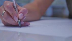 Mänskliga händer med blyertspennahandstil på papper på vit tabellbakgrund arkivfilmer