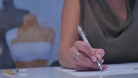 Mänskliga händer med blyertspennahandstil på papper på vit tabellbakgrund lager videofilmer