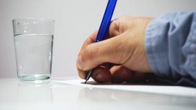 Mänskliga händer skriver på ark av papper och dricker ett exponeringsglas av vatten Skriva brev arkivfilmer