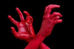 Mänskliga händer som målas i rött, poserar på en svart bakgrund Arkivbild