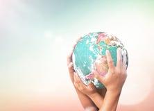 Mänskliga händer som rymmer den gröna planeten Royaltyfri Bild