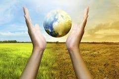 Mänskliga händer som rymmer ett jordklot arkivfoton