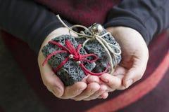 Mänskliga händer som rymmer julkol Arkivfoton
