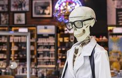 Mänskligt skelett i en vit medicinsk kappa och svarta exponeringsglas royaltyfri bild
