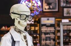 Mänskligt skelett i en vit medicinsk kappa och svarta exponeringsglas royaltyfri fotografi