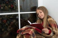 Märchen für fröhliche Feiertage Der kleine Leser, der im Plaid eingewickelt wird, sitzen auf Fensterbrett Wenig Mädchen genießen, stockbilder