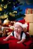Märchenporträt des Weihnachtsnetten kleinen Babys, das wie Weihnachtsmann am Hintergrund des neuen Jahres unter Baum trägt Stockfotos