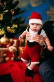 Märchenporträt des Weihnachtsnetten kleinen Babys, das wie Weihnachtsmann am Hintergrund des neuen Jahres unter Baum trägt Lizenzfreie Stockfotos