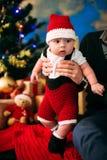 Märchenporträt des Weihnachtsnetten kleinen Babys, das wie Weihnachtsmann am Hintergrund des neuen Jahres unter Baum trägt Lizenzfreies Stockbild