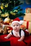 Märchenporträt des Weihnachtsnetten kleinen Babys, das wie Weihnachtsmann am Hintergrund des neuen Jahres unter Baum trägt Stockbild