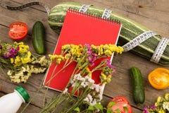 märgsquash, måttband, tom röd notepad, flaska av vatten, blommor, tomater och gurkor på den bruna trätabellen Royaltyfria Foton