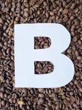märka B i vit och bakgrund med grillade kaffebönor, bakgrund och textur royaltyfri bild
