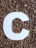 märka C i vit och bakgrund med grillade kaffebönor, bakgrund och textur arkivbilder