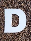 märka D i vit och bakgrund med grillade kaffebönor, bakgrund och textur royaltyfria foton