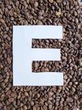 märka E i vit och bakgrund med grillade kaffebönor, bakgrund och textur arkivbilder