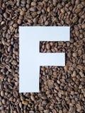 märka F i vit och bakgrund med grillade kaffebönor, bakgrund och textur royaltyfria foton