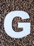 märka G i vit och bakgrund med grillade kaffebönor, bakgrund och textur royaltyfria foton