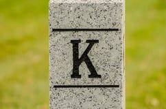 Märka G som snidas in i stenstolpen Arkivfoto