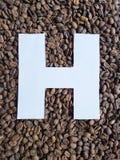 märka H i vit och bakgrund med grillade kaffebönor, bakgrund och textur arkivfoto