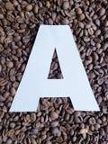 märka A i vit och bakgrund med grillade kaffebönor, bakgrund och textur royaltyfri foto