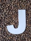 märka J i vit och bakgrund med grillade kaffebönor, bakgrund och textur royaltyfria bilder