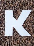 märka K i vit och bakgrund med grillade kaffebönor, bakgrund och textur arkivfoto