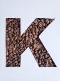 märka K med grillade kaffebönor och vit bakgrund royaltyfri bild