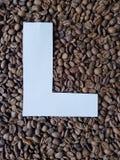 märka L i vit och bakgrund med grillade kaffebönor, bakgrund och textur royaltyfri bild