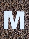 märka M i vit och bakgrund med grillade kaffebönor, bakgrund och textur royaltyfri fotografi